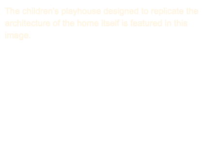 The children's playhouse designed to replicate the architecture of the home itself is featured in this image.